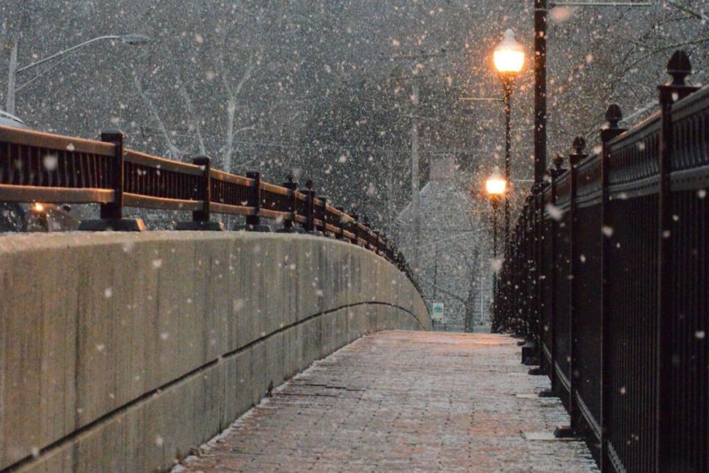 Snow falling on a walking bridge